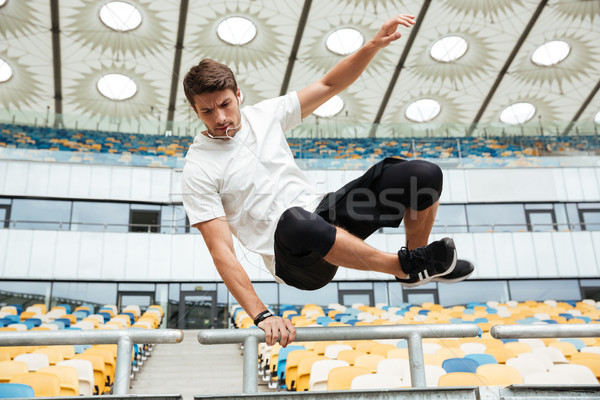 Sports man jumping at the stadium outdoors Stock photo © deandrobot