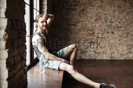 Side view of a sportsman doing exercises at the windowsill Stock photo © deandrobot