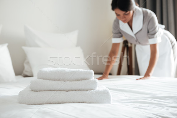 Young hotel maid setting up pillow on bed Stock photo © deandrobot
