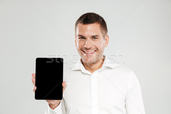 Cheerful young man showing display of tablet computer. Stock photo © deandrobot