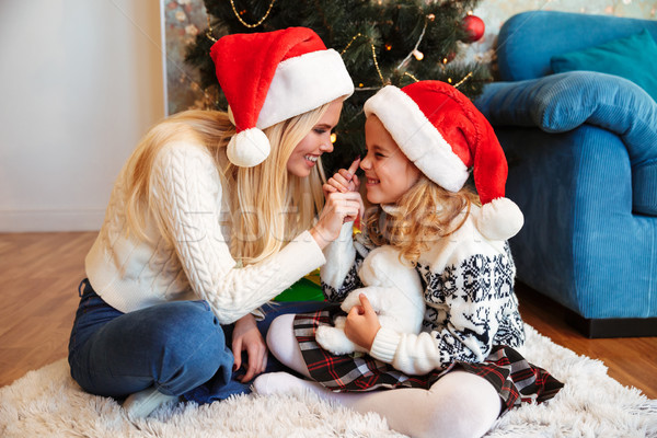 Cheerful blonde woman in Santa's hat touching daughters nose whi Stock photo © deandrobot