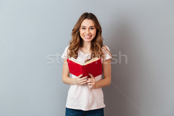 Portrait of a smiling young girl holding book Stock photo © deandrobot