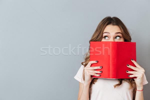 Portré csinos fiatal lány rejtőzködik mögött nyitott könyv Stock fotó © deandrobot
