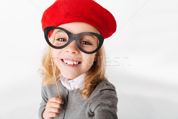 Portrait of a smiling little schoolgirl dressed in uniform Stock photo © deandrobot