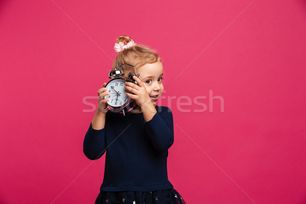 Intrigued young blonde girl holding alarm clock in studio Stock photo © deandrobot