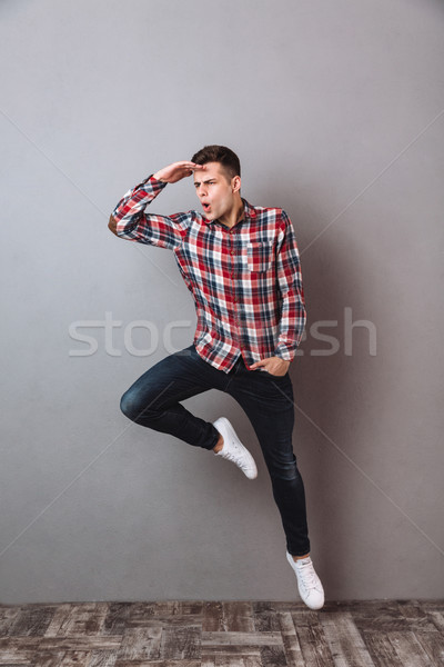 Full length image of man in shirt and jeans jumping Stock photo © deandrobot