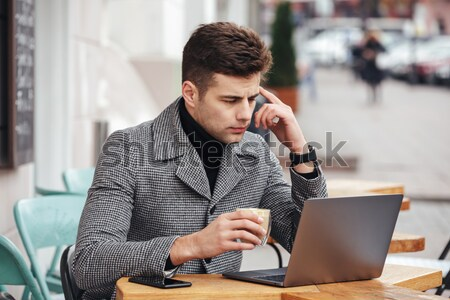 Photo of handsome man in gray coat smoking cigarette, and drinki Stock photo © deandrobot