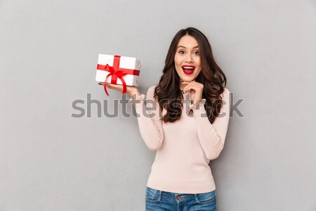 Smiling woman in sweater holding gift box on the palm Stock photo © deandrobot