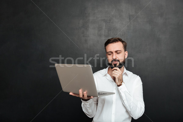 Portrait of concentrated unshaved guy looking at silver laptop a Stock photo © deandrobot
