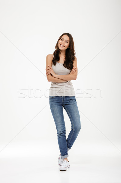 Full length image of Happy brunette woman posing with crossed arms Stock photo © deandrobot