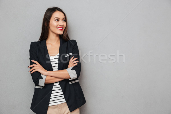 Smiling asian business woman with crossed arms looking away Stock photo © deandrobot