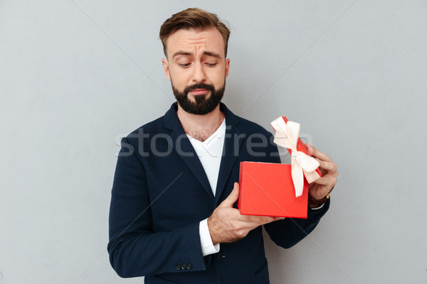 Image of Surprised bearded man in business clothes opening gift Stock photo © deandrobot