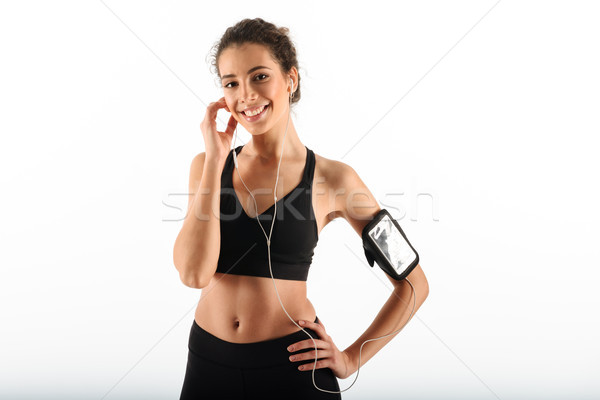 Happy curly brunette fitness woman holding arm on hip Stock photo © deandrobot