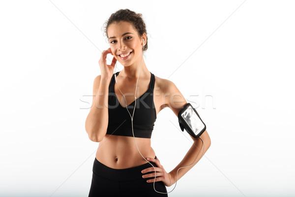 Boldog fürtös barna hajú fitnessz nő tart kar Stock fotó © deandrobot