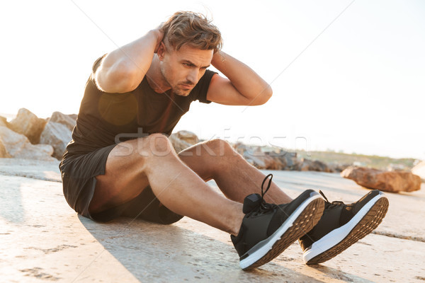 Portrait of a concentrated sportsman doing abs Stock photo © deandrobot