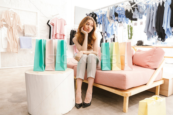 Tired young woman sitting at the clothing store Stock photo © deandrobot