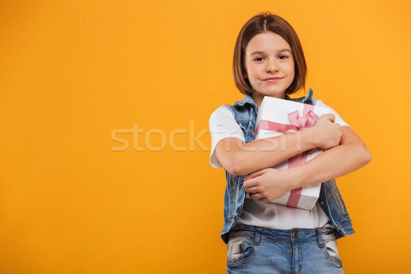 Portré elégedett kicsi iskolás lány tart ajándék doboz Stock fotó © deandrobot