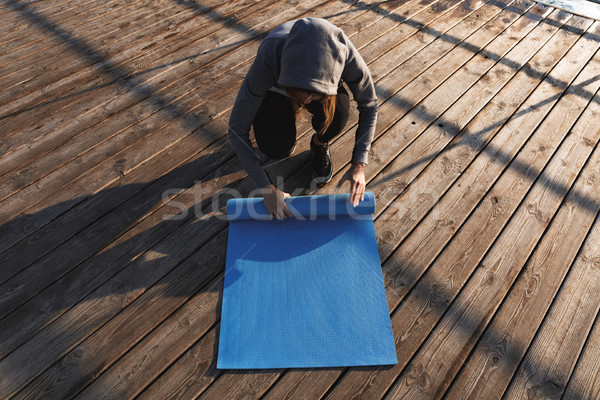 Top view of a woman unwrapping fitness mat Stock photo © deandrobot