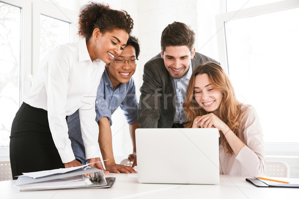Group of cheerful young multiethnic businesspeople Stock photo © deandrobot