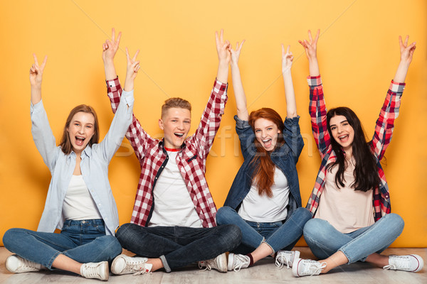 Group of young positive school friends sitting with hands raised Stock photo © deandrobot
