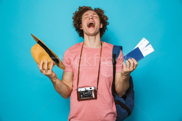 Photo of joyful voyage man 18-20 with curly hair wearing backpac Stock photo © deandrobot