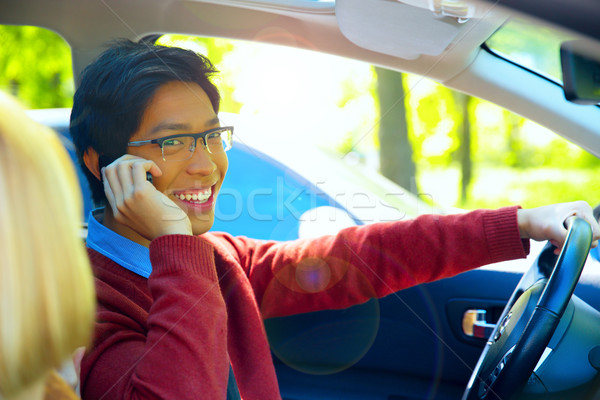 Young happy man driving car and speaking on mobile phone Stock photo © deandrobot