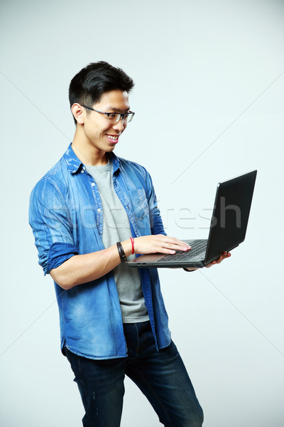 Happy asian man using laptop on gray background Stock photo © deandrobot