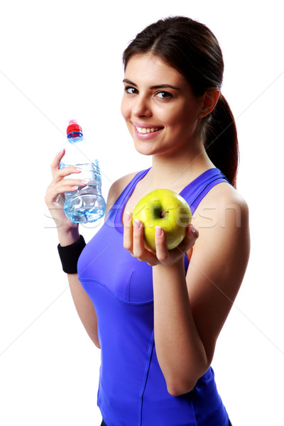 Young smiling sport woman holding bottle of water and apple isolated on white background Stock photo © deandrobot