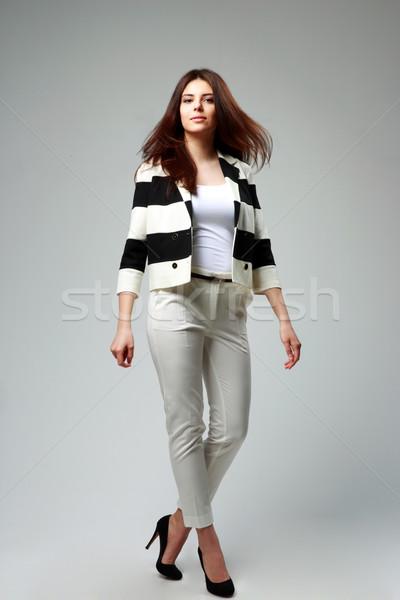Stúdiófelvétel fiatal gyönyörű nő lezser ruházat szürke Stock fotó © deandrobot