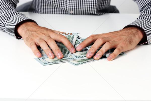 Mężczyzna ręce utrzymać dolarów tabeli Zdjęcia stock © deandrobot