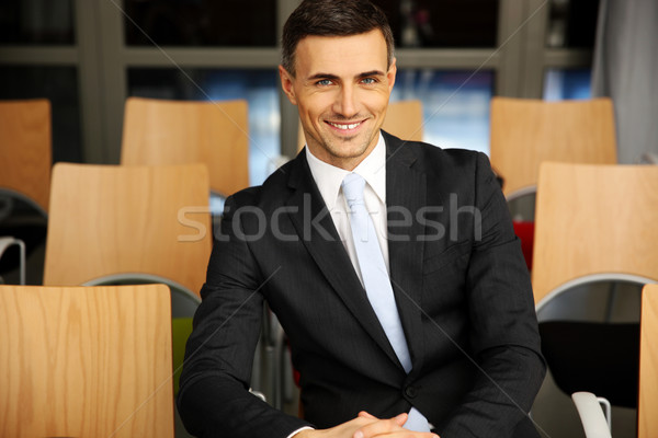 Cheerful businessman sitting at conference hall Stock photo © deandrobot