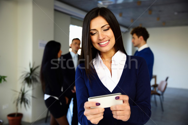 Cheerful businesswoman using smartphone in front of colleagues Stock photo © deandrobot