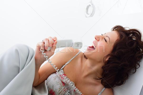 Mutlu genç kadın şarkı söyleme telefon yatak telefon Stok fotoğraf © deandrobot
