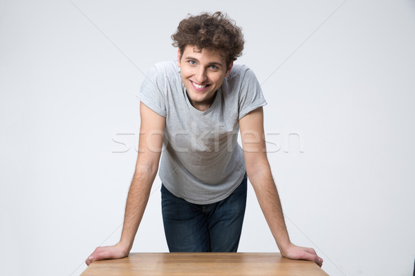 Happy young male student standing and leaning on the table Stock photo © deandrobot