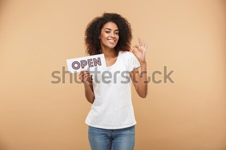 Smiling young woman showing tablet computer screen over gray background Stock photo © deandrobot