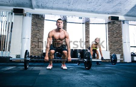 Fit man and woman workout at gym Stock photo © deandrobot