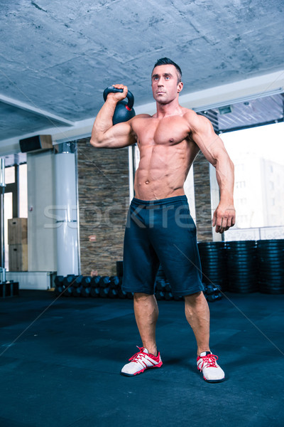 Bodybuilder workout with kettle ball in crossfit gym Stock photo © deandrobot