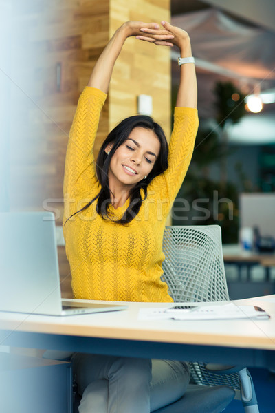 Businesswoman sitting at the table and stretching hands Stock photo © deandrobot