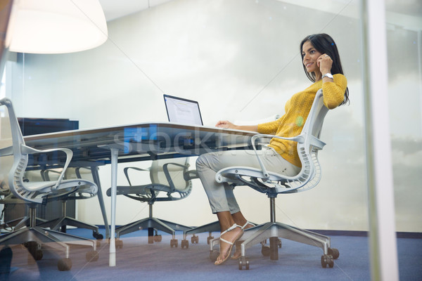 Businesswoman talking on the phone in office Stock photo © deandrobot