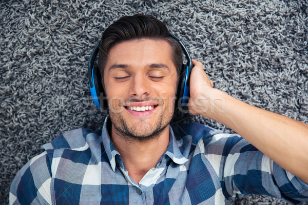 Man lying on the floor with headphones at home Stock photo © deandrobot