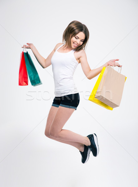 Happy girl jumping with shopping bags Stock photo © deandrobot