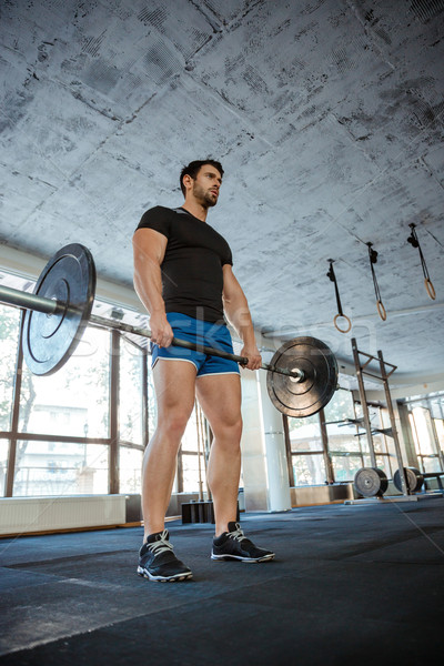 Male bodybuilder workout with barbell Stock photo © deandrobot