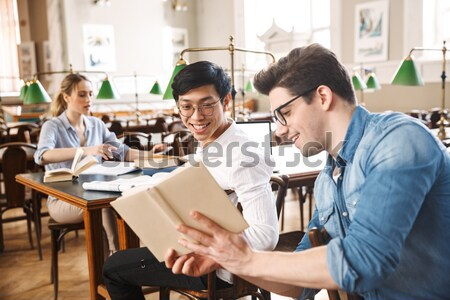 Smiling happy young curly male working in team using notebook Stock photo © deandrobot