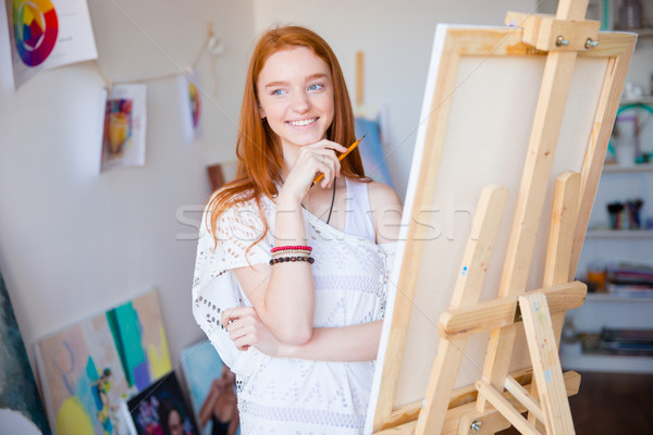 Happy inspired female artist drawing with pencil in art class Stock photo © deandrobot