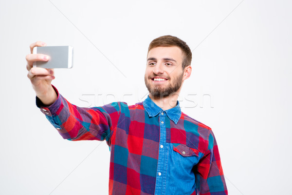 Cheerful confident young man taking selfie using mobile phone  Stock photo © deandrobot