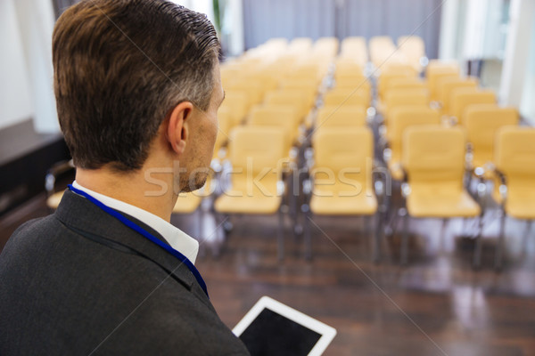 Businessman holding tablet in empty conference hall Stock photo © deandrobot