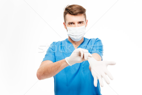 Male surgeon putting on gloves Stock photo © deandrobot