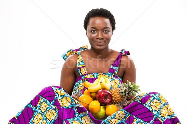 Cheerful beautiful african american young woman sitting and holding fruits  Stock photo © deandrobot