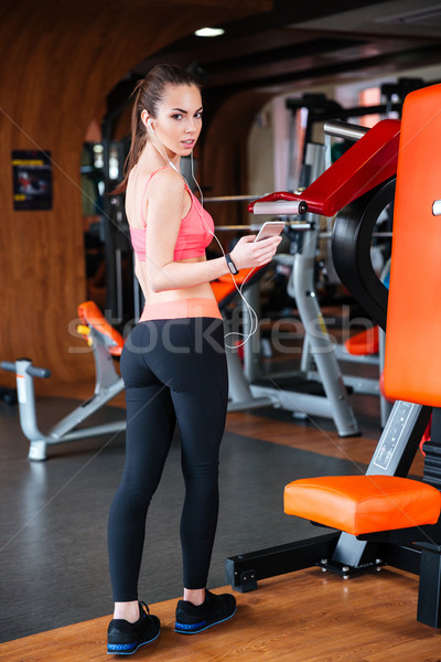 Sportswoman standing and listening to music from smartphone in gym Stock photo © deandrobot