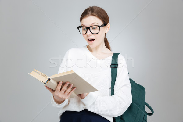 Surprised cute girl student in glasses with backpack reading book Stock photo © deandrobot
